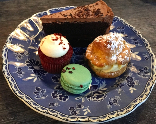 Second plate of pastries: chocolate cake, cream puff, macaron, cupcake